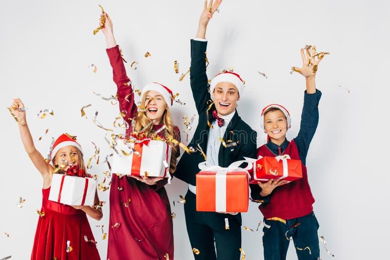 Молодая счастливая рождественская семья с детьми в шляпах Санта-Клауса, весело проводящими рождественские подарки на белом фоне стоковые изображения rf