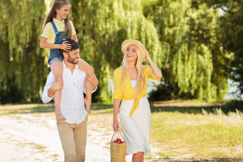 Молодая счастливая семья идя на парк стоковые фотографии rf