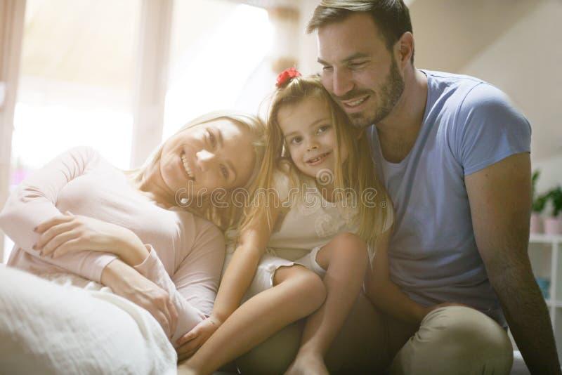 Молодая счастливая семья наслаждаясь дома стоковое изображение rf
