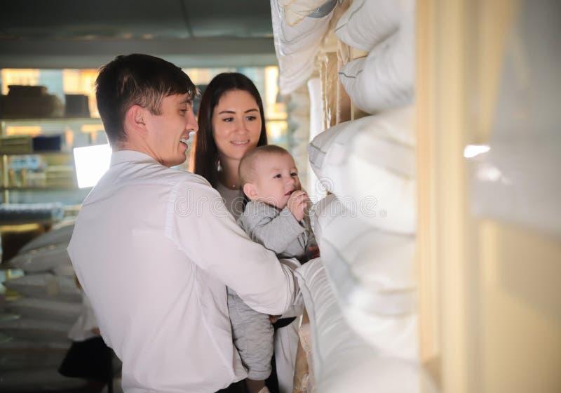 Молодая счастливая семья на покупках Женатые пары и младенец идя в магазин ткани стоковые фотографии rf