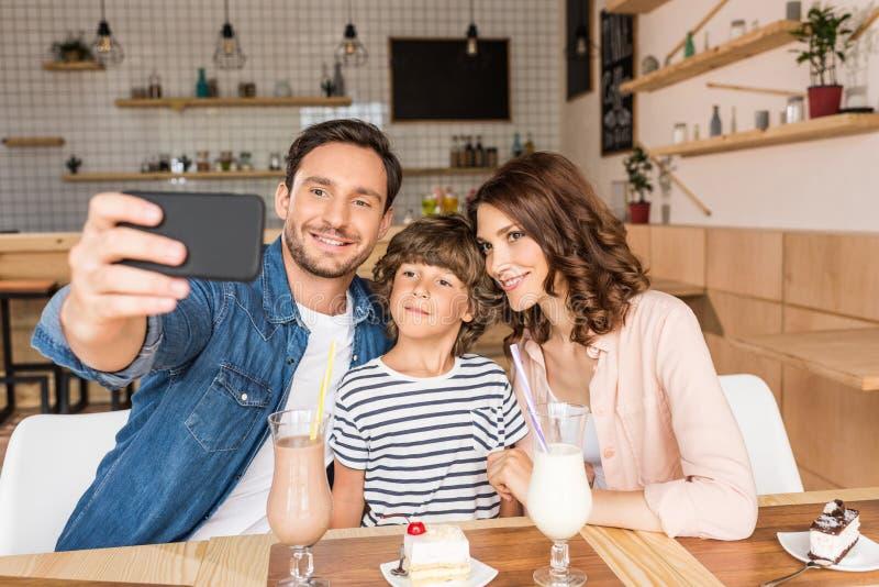 молодая счастливая семья принимая selfie в кафе с десертами стоковое фото