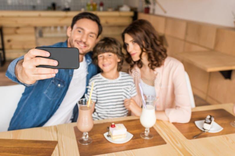 молодая счастливая семья принимая selfie в кафе с десертами стоковые изображения rf