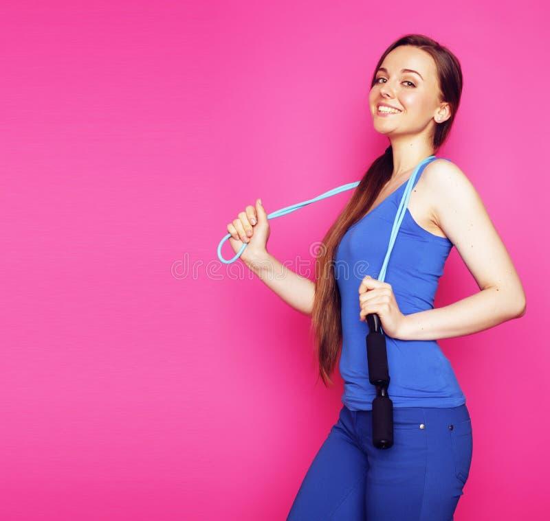 Молодая счастливая тонкая девушка с прыгая веревочкой на розовой предпосылке стоковые фото