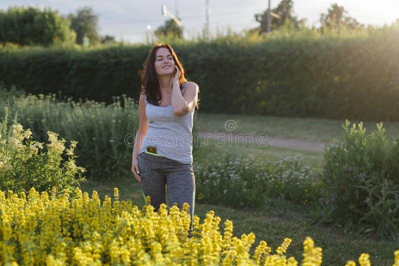 Молодая счастливая sporty женщина в sportswear отдыхая после jogging в парке города стоковое изображение