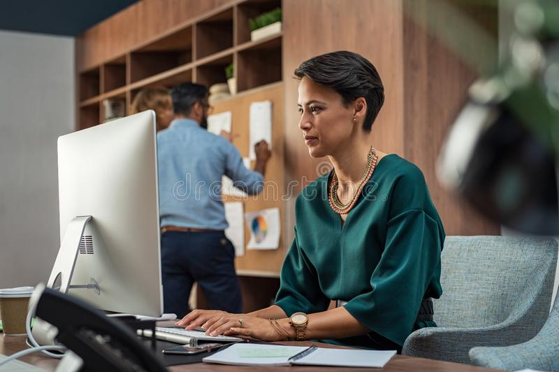 Молодая творческая женщина работая на компьютере стоковое изображение rf