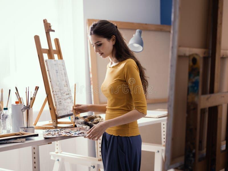 Молодая творческая картина художника в студии стоковое фото rf