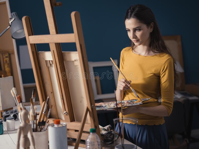 Молодая творческая картина художника в студии стоковые изображения rf