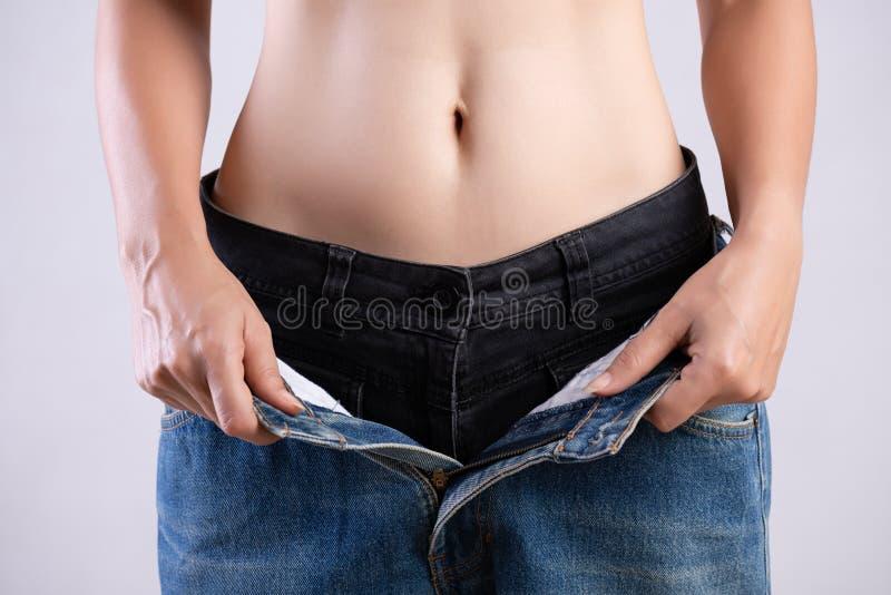 Молодая тонкая женщина в слишком больших голубых джинсах Женщина пригонки нося слишком большие брюки Здравоохранение и концепция  стоковые изображения rf