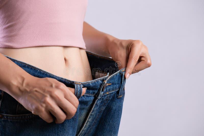 Молодая тонкая женщина в слишком больших голубых джинсах Женщина пригонки нося слишком большие брюки Здравоохранение и концепция  стоковое фото rf