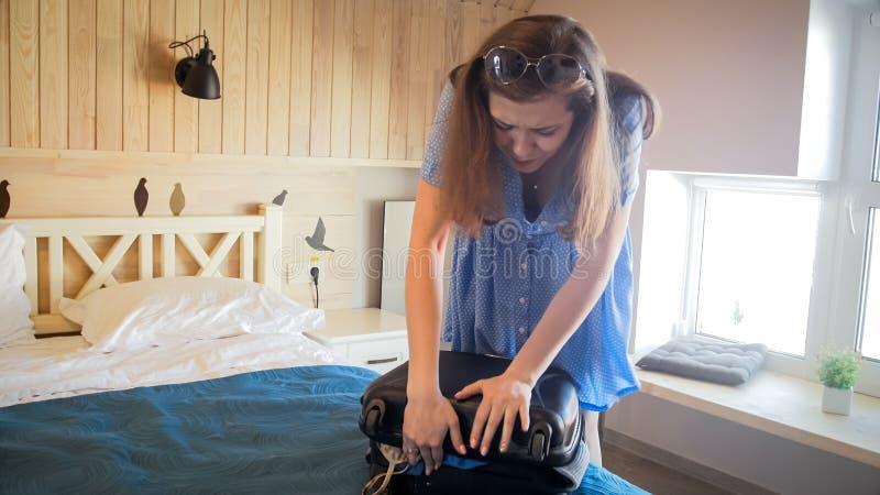 Молодая туристская девушка пробуя закрыть полный чемодан в гостиничном номере стоковые изображения