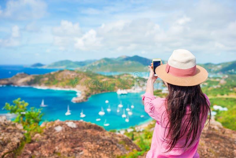 Молодая туристская женщина делая фото английской гавани от высот Ширли, Антигуы, залива рая на тропическом острове в стоковые фото