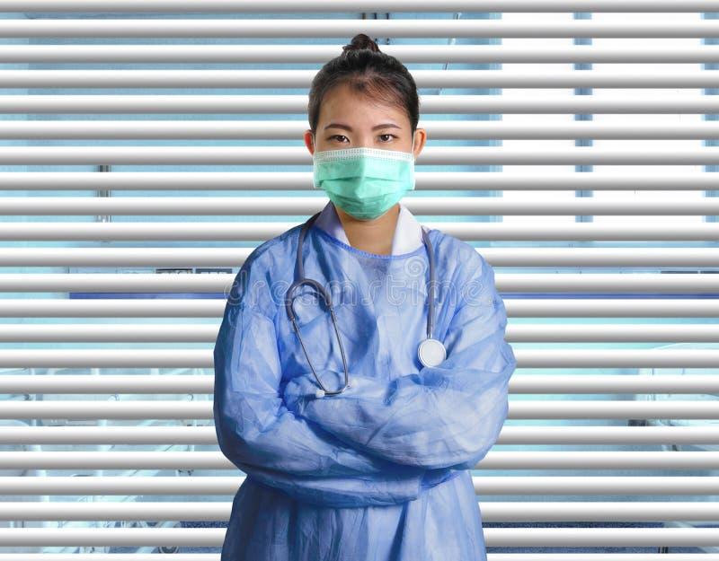 Молодая уверенная и успешная азиатская женщина доктора китайской медицины в больнице scrubs и маска представляя на венецианских ш стоковое изображение rf
