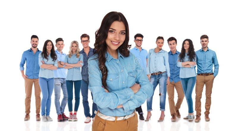 Молодая уверенно женщина стоя перед ее вскользь группой стоковое фото rf