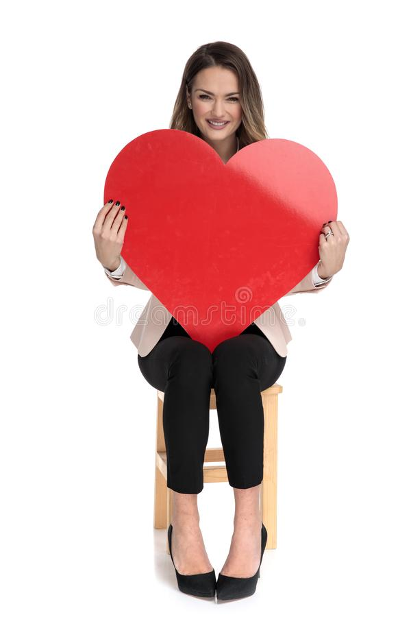 Молодая умная случайная женщина держит большое сердце дня Валентайн стоковые фото