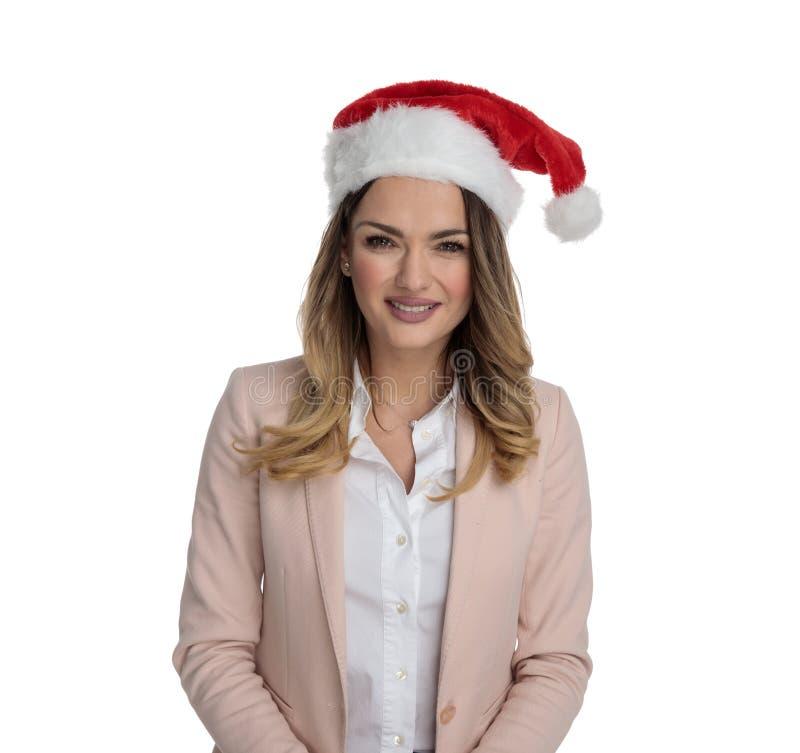 Молодая умная случайная женщина нося розовые костюм и шляпу santa стоковое изображение