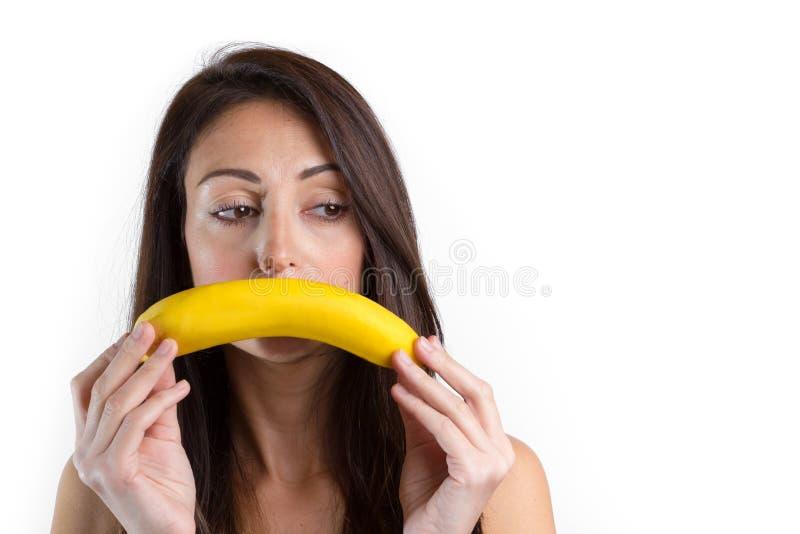 Молодая унылая женщина с бананом стоковое изображение