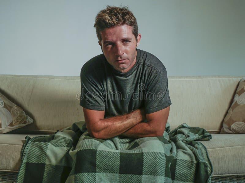 Молодая унылая и отчаянная комната человека дома живущая сидя на кресле софы смотря эмоциональное страдая чувство депрессии и нер стоковые фотографии rf