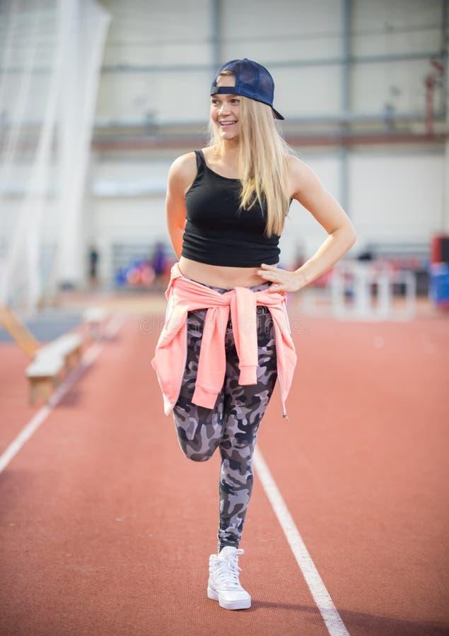 Молодая усмехаясь атлетическая женщина протягивая ее ноги стоковые фотографии rf