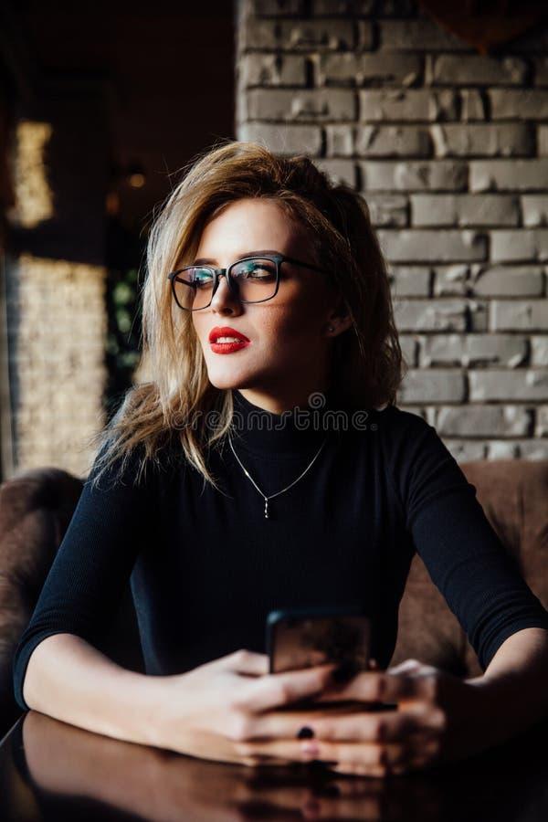 Молодая усмехаясь бизнес-леди сидя в кафе на таблице, полагаясь руке на таблице и держа smartphone стоковое изображение