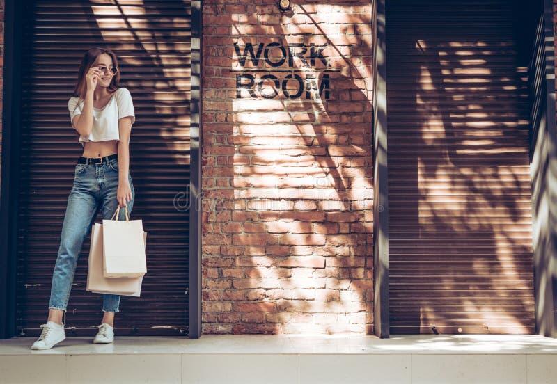 Молодая усмехаясь девушка в солнечных очках с хозяйственной сумкой на коричневом металле закрывает предпосылку стоковое изображение