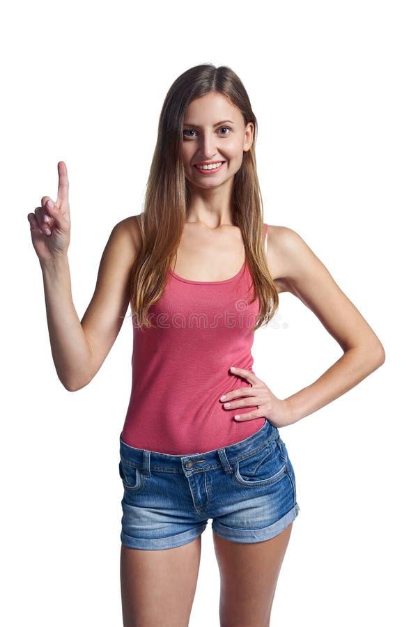 Молодая усмехаясь девушка указывая ее палец вверх стоковое фото rf