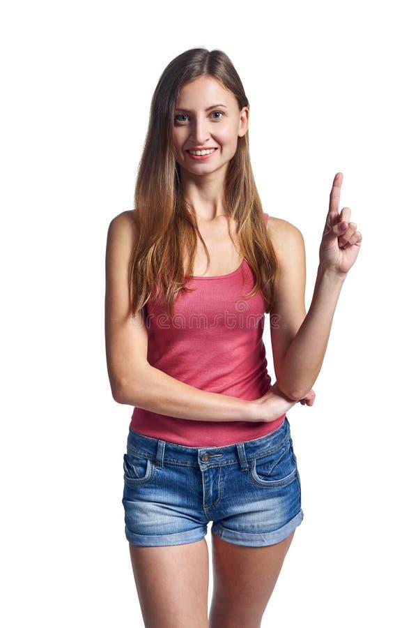 Молодая усмехаясь девушка указывая ее палец вверх стоковая фотография