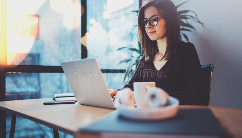 Молодая усмехаясь деятельность стекел глаза девушки нося на компьтер-книжке на ее рабочем месте на офисе ночи горизонтально запач стоковые фото