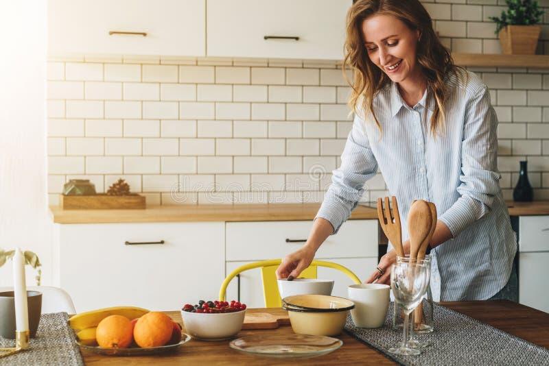 Молодая усмехаясь домохозяйка стоя в кухне около таблицы варит обедающий, очищая блюда Девушка делает завтрак стоковое изображение