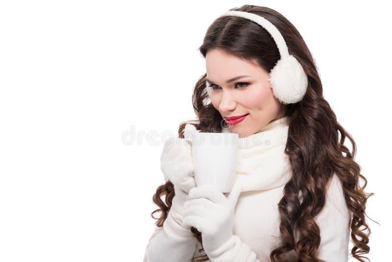 молодая усмехаясь женщина в одежде зимы выпивая от кружки кофе, стоковые изображения