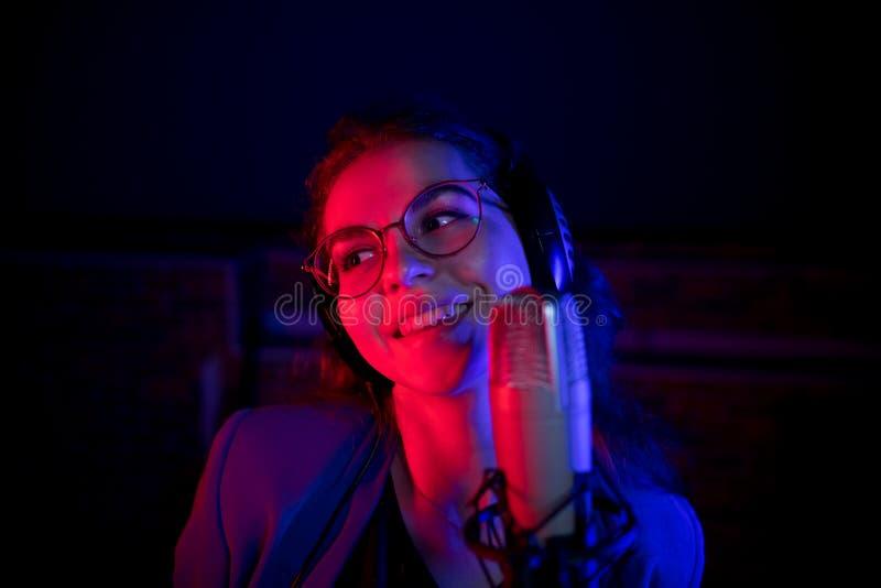 Молодая усмехаясь женщина в стеклах поя микрофоном в неоновом освещении стоковая фотография