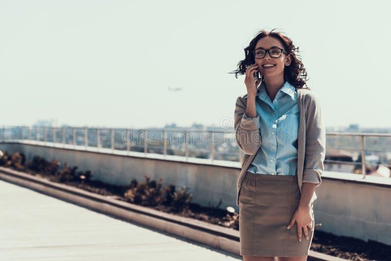 Молодая усмехаясь женщина говоря на мобильном телефоне внешнем стоковое фото