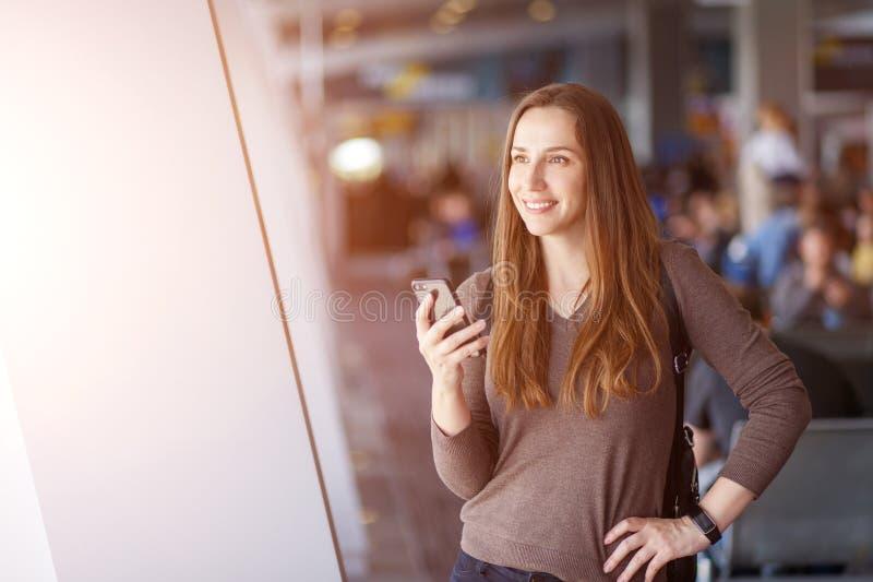 Молодая усмехаясь женщина используя смартфон в аэропорте стоковое изображение rf