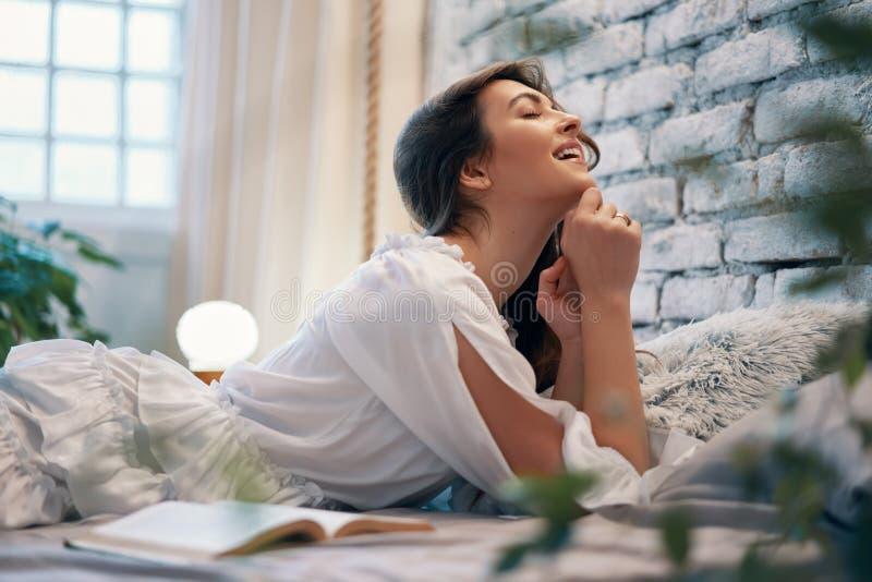 Молодая усмехаясь женщина ослабляя в ее неудаче на современном доме стоковое фото rf