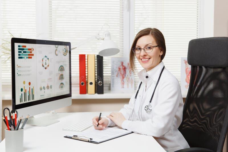 Молодая усмехаясь женщина сидя на столе, работая на компьютере с медицинскими документами в светлом офисе в больнице женщина стоковое фото rf