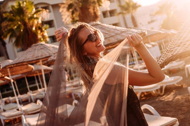 Молодая усмехаясь женщина со светлой тканью в оконтуренном солнечном свете на пляже стоковое фото rf