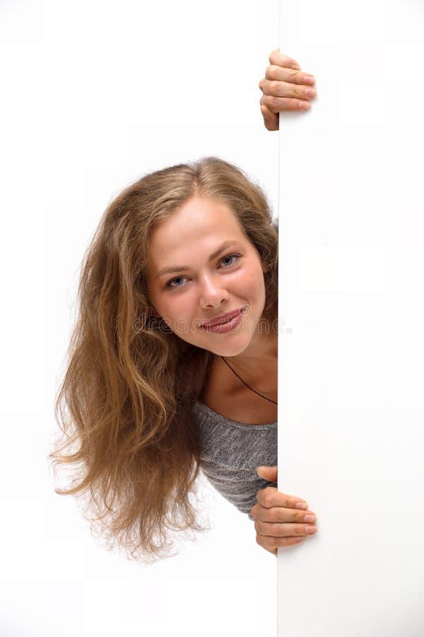 Молодая усмехаясь женщина с пустой доской, держит руки на плакате стоковые фото