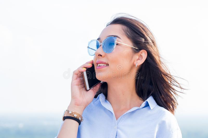 Молодая усмехаясь женщина с солнечными очками и желтым маникюром говоря на мобильном телефоне стоковое изображение rf