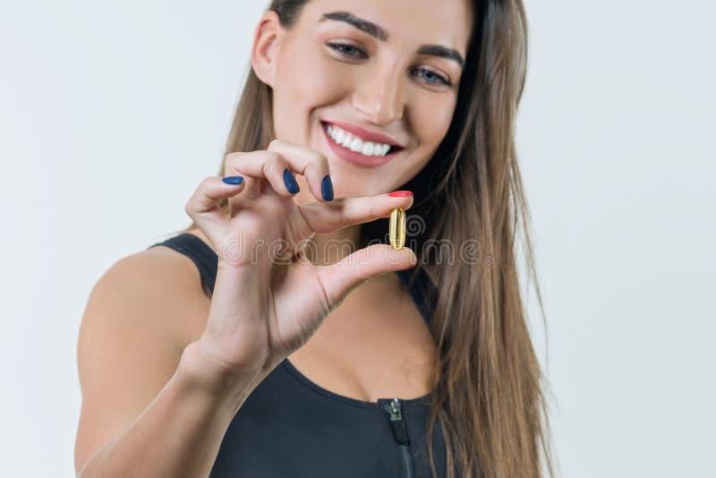 Молодая усмехаясь красивая здоровая женщина в sportswear с Витамином D, e, капсулами рыбьего жира omega-3, на белой предпосылке стоковые изображения