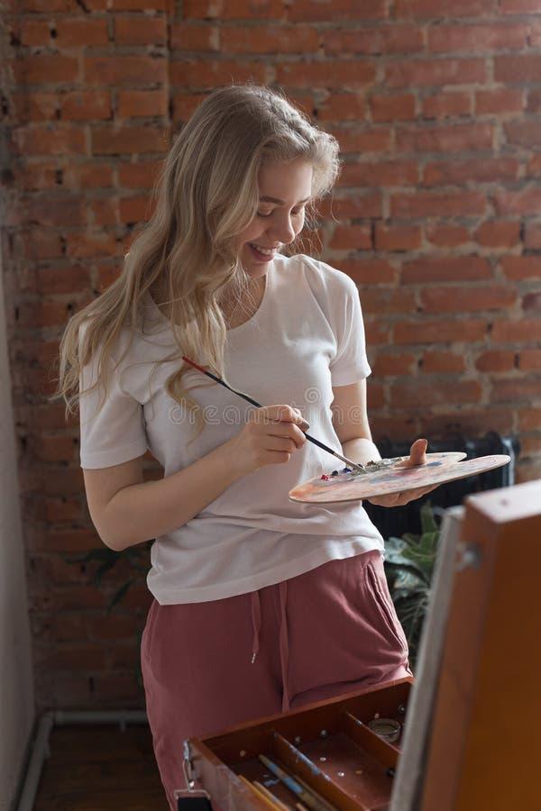 Молодая усмехаясь милая белокурая девушка с цветами щетки смешивая на стоковое фото