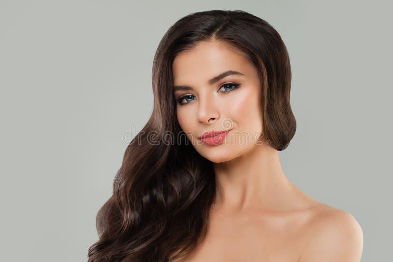 Молодая усмехаясь модель спа женщины со здоровой кожей и длинным вьющиеся волосы Haircare и предпосылка skincare стоковые фотографии rf