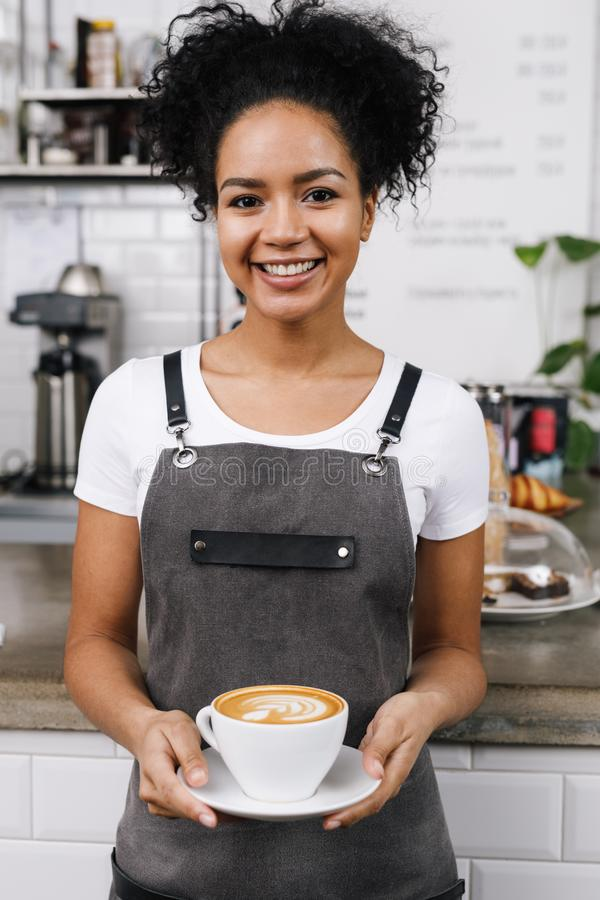 Молодая усмехаясь официантка держа чашку latte стоковое фото rf