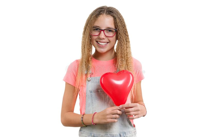 Молодая усмехаясь предназначенная для подростков девушка поздравляя на празднике с красным воздушным шаром сердца на изолированно стоковое изображение