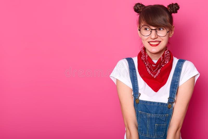 Молодая усмехаясь сладкая девушка смотря в сторону, нося случайная белая футболка, прозодежды джинсов, красный bandana и круглые  стоковые изображения