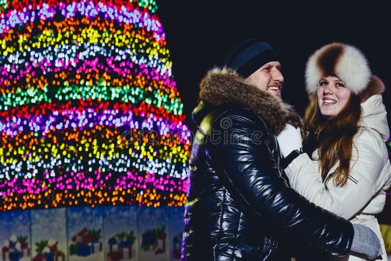 Молодая усмехаясь счастливая пара обнимая на улице рождества стоковое изображение rf