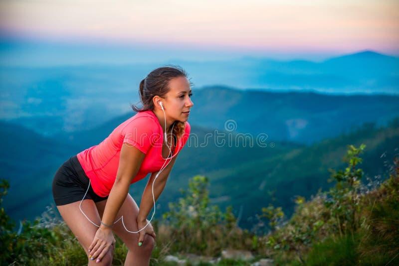 Молодая утомленная женщина во время следа бежать в горах стоковая фотография