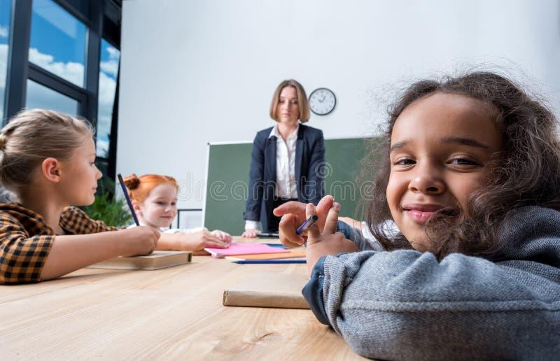молодая учительница смотря многонациональные школьников стоковая фотография rf