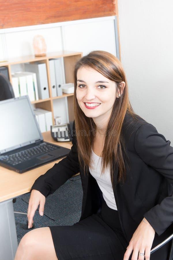 Молодая финансовая коммерсантка сидя на его рабочем месте перед компьтер-книжкой компьютера стоковые фотографии rf