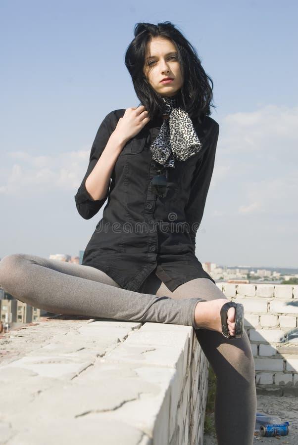Молодая холодная женщина ослабляет на крыше стоковое изображение