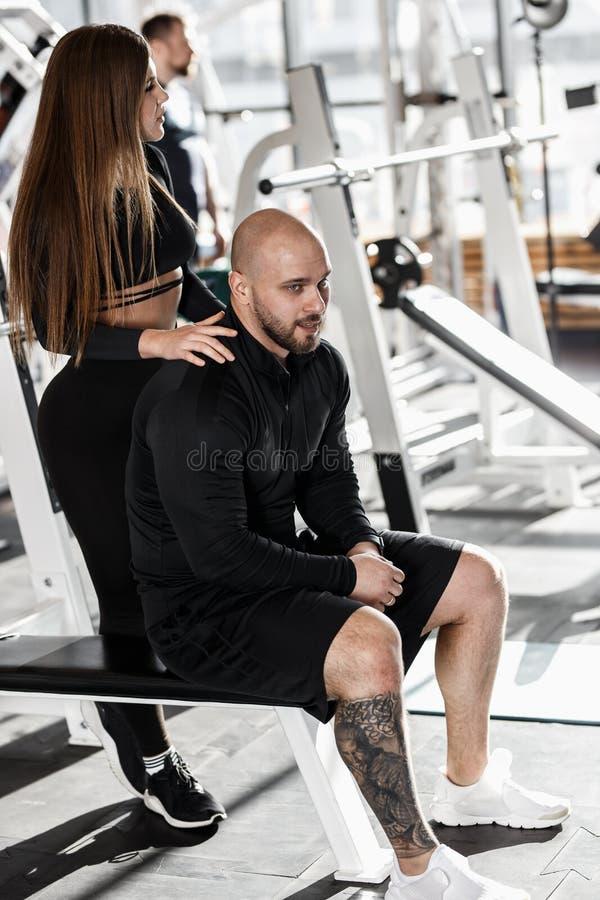 Молодая худенькая милая девушка стоит за атлетическим человеком сидя на стенде пятна и держит ее руки на его плечах стоковые фото