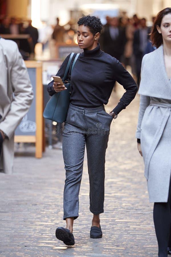 Молодая черная коммерсантка идя в улицу в Лондоне используя смартфон, выборочный фокус стоковые изображения rf